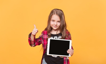 child and technology concept. Small girl with tablet pc computers blank black screen showing ok sign over yellow color background