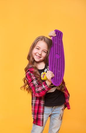 Beautiful teen girl with her birthday gift over yellow background. Happy preschool little kid holding brand new skateboard. Vertical portraot Stock Photo