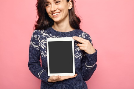Woman holding a tablet with empty black screen over pink color background. Smiling girl in winter clothes showing display with copy space for app content