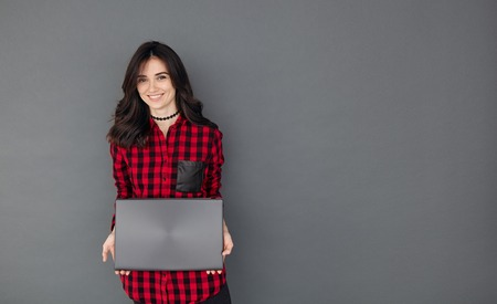 Smiling pretty teen student girl with laptop pc computer standing at grey wall with blank space