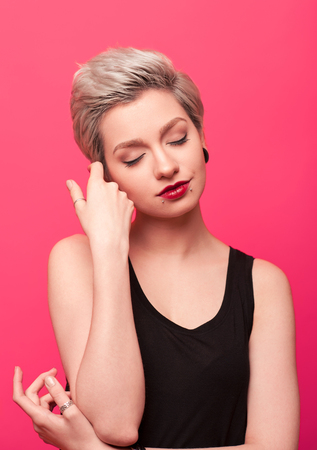closeup portrait of young pretty blond woman on pink background