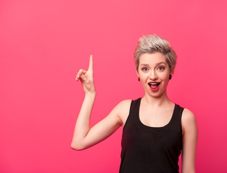 Model with blond short hair pointing up on pink Stock Photo