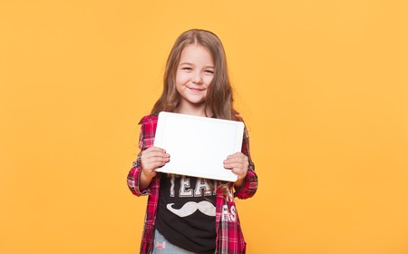 Smiling little girl holding up a blank tablet computer Stock Photo