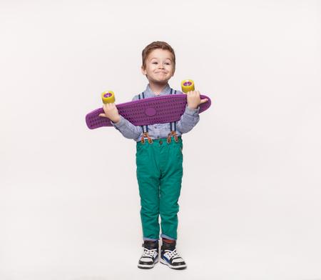 Stylish kid boy holding his birthday gift skateboard Stock Photo