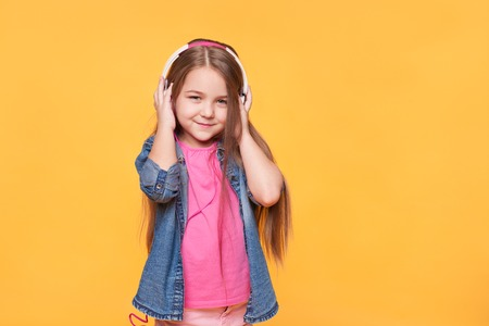 Portrait of cute little girl listening to music over yellow