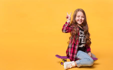 happy child girl laughing while sitting on skateboard Stock Photo