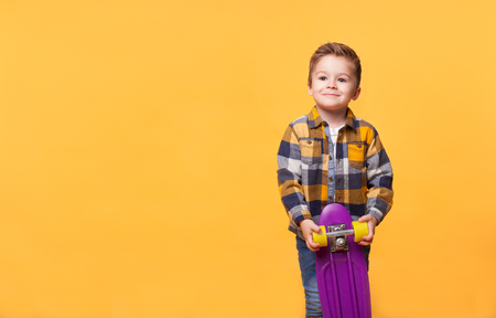 smiling little boy standing with skateboard