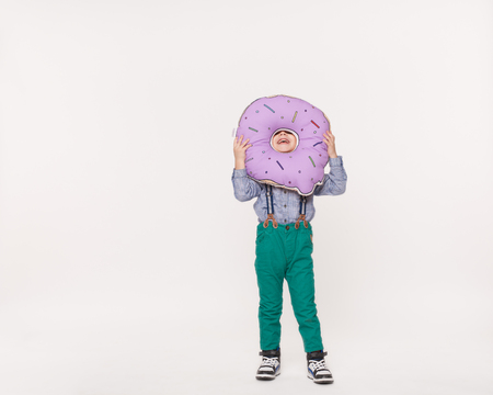 kid boy playing with toy pillow in shape of donut