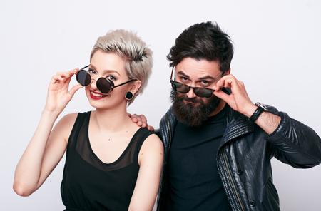 homem barbudo jovem e uma mulher loura na moda que olha a câmera