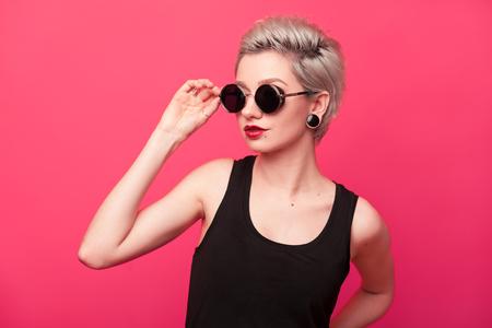 Stylish fashion portrait of young woman on pink background