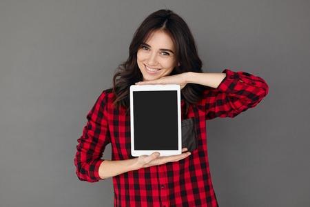 Casual happy Woman Showing Digital Tablet With Blank Screen Banco de Imagens