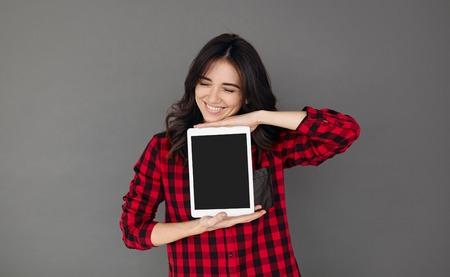 Mulher na camisa ocasional showig tela de computador em branco comprimido vermelho Banco de Imagens