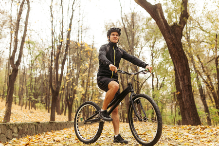 Man on cycle in autumn park