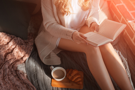 Woman with beverage reading a book