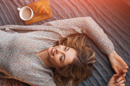 Woman lying on bed with beverage Фото со стока