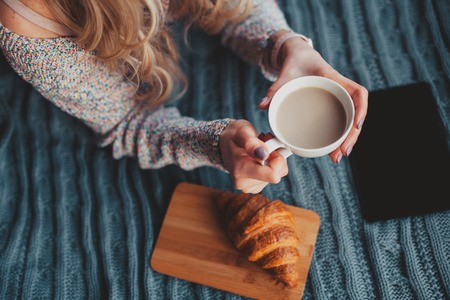 Girl holding a cocoa cup on bed