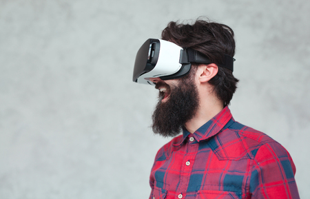Cheerful man in VR helmet Фото со стока