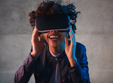 Smiling woman touching VR goggles