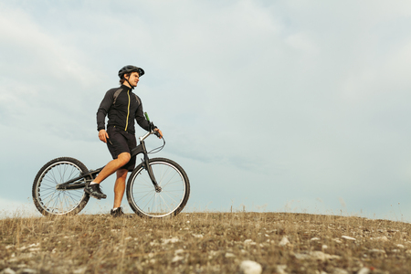 Man on bicycle standing on hill Stock Photo