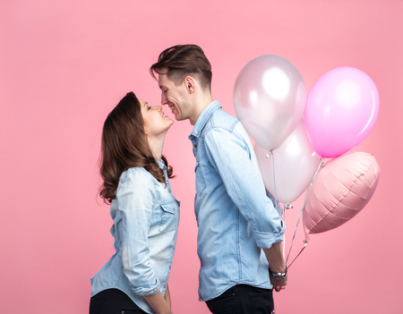 Young couple posing on pink