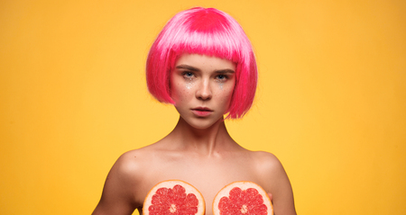 Pretty woman covering breasts with grapefruit Stock Photo
