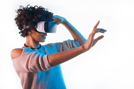 Pretty woman wearing VR goggles touching air
