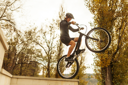 Man balancing on a bicycle in park