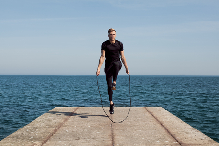 Man jumping rope on pier Stock Photo
