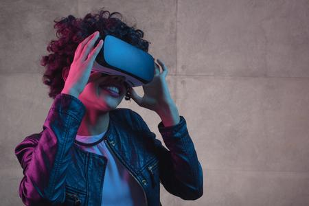 Young girl touching VR helmet Imagens