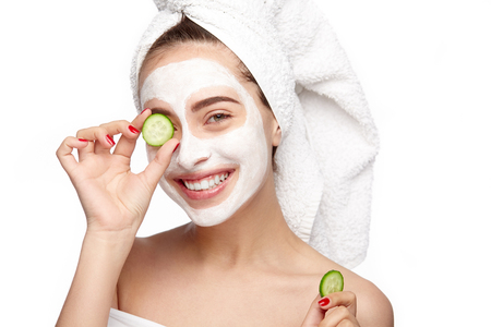 Woman moisturizing eye with cucumber