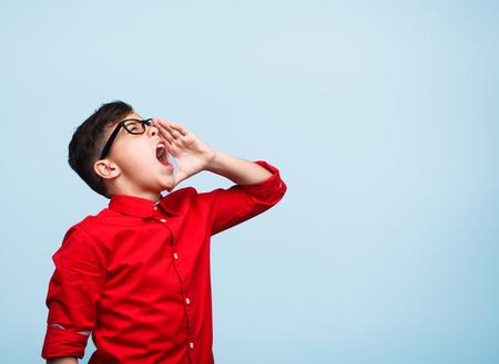 loud: Young boy in glasses shouting loud Stock Photo