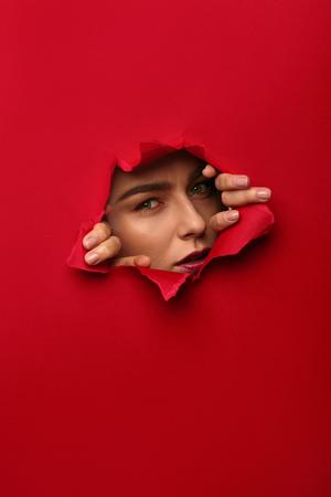 Woman posing in hole in paper Фото со стока