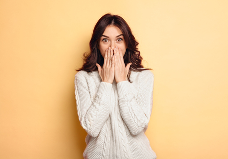 Young brunette in white sweater posing on beige background with hands on face looking excited.  Foto de archivo