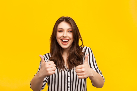 Delighted woman posing with thumbs up Stockfoto