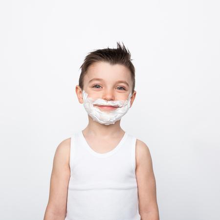 Content boy in shaving foam 免版税图像