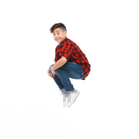 Little boy jumping on white background