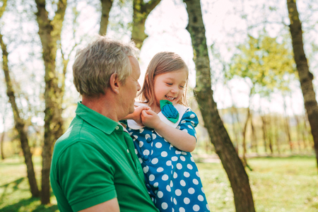 grandkids: Grandfather holding girl on hands
