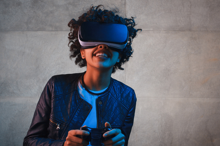 Smiling woman with gamepad and VR goggles
