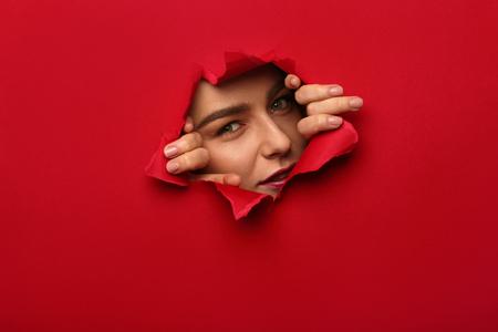 紙の穴から外を眺める少女