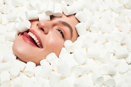 Smiling woman in marshmallows Stock Photo
