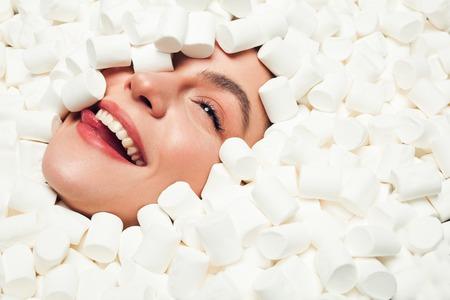 Smiling woman in marshmallows Фото со стока