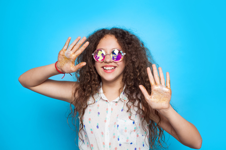 Smiling girl with hands in glitter