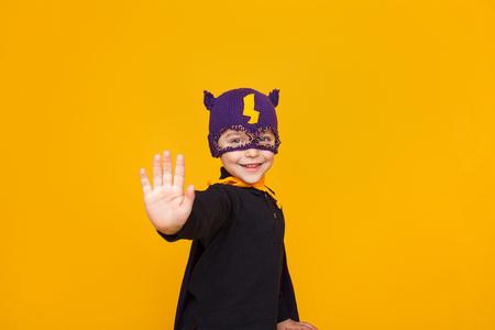 子供のスーパー ヒーローのオレンジのポーズで