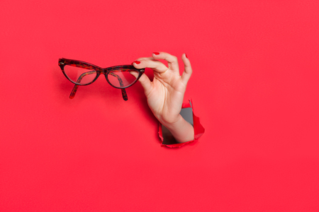 anonymous people: Female hand in paper hole with glasses