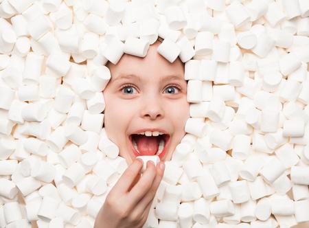 흰색 마쉬 멜 로우에서 포즈 쾌활한 아이