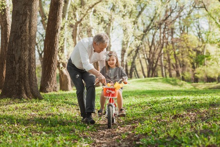 Laughing girl riding bicycle with grandfather
