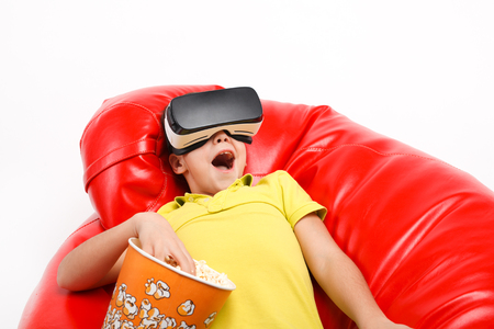 Kid with popcorn enjoying virtual reality Фото со стока