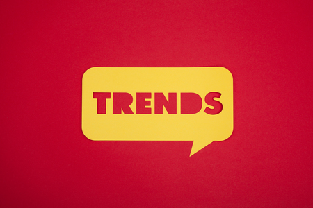 From above yellow bubble with trends word isolated on red.