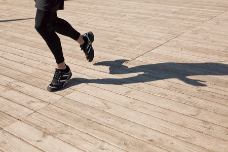Unrecognizable sportsman jogging on wooden board floor in sunny day. Фото со стока