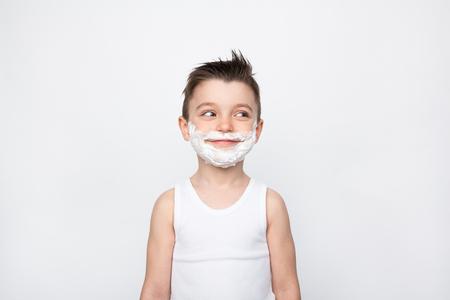 얼굴에 거품을 면도하는 소년